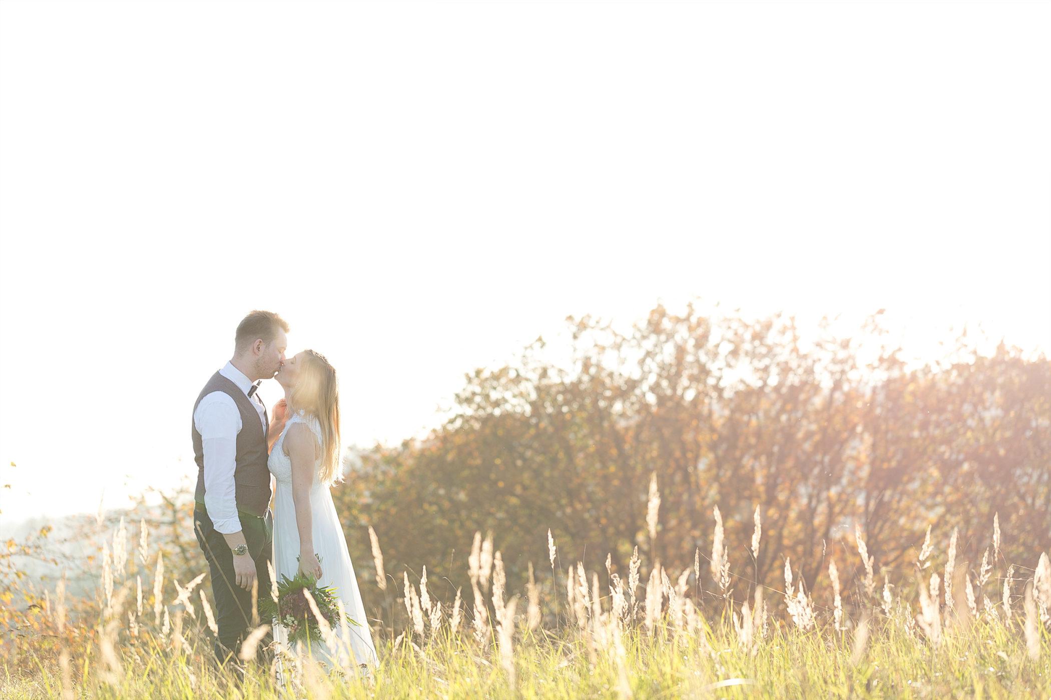 Küssendes Hochzeitspaar auf einer Wiese im Gegenlicht.