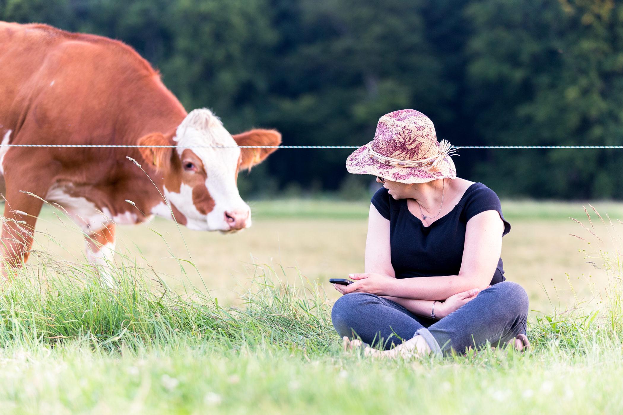 Frau mit Hut beobachtet und spricht mit einer Kuh.