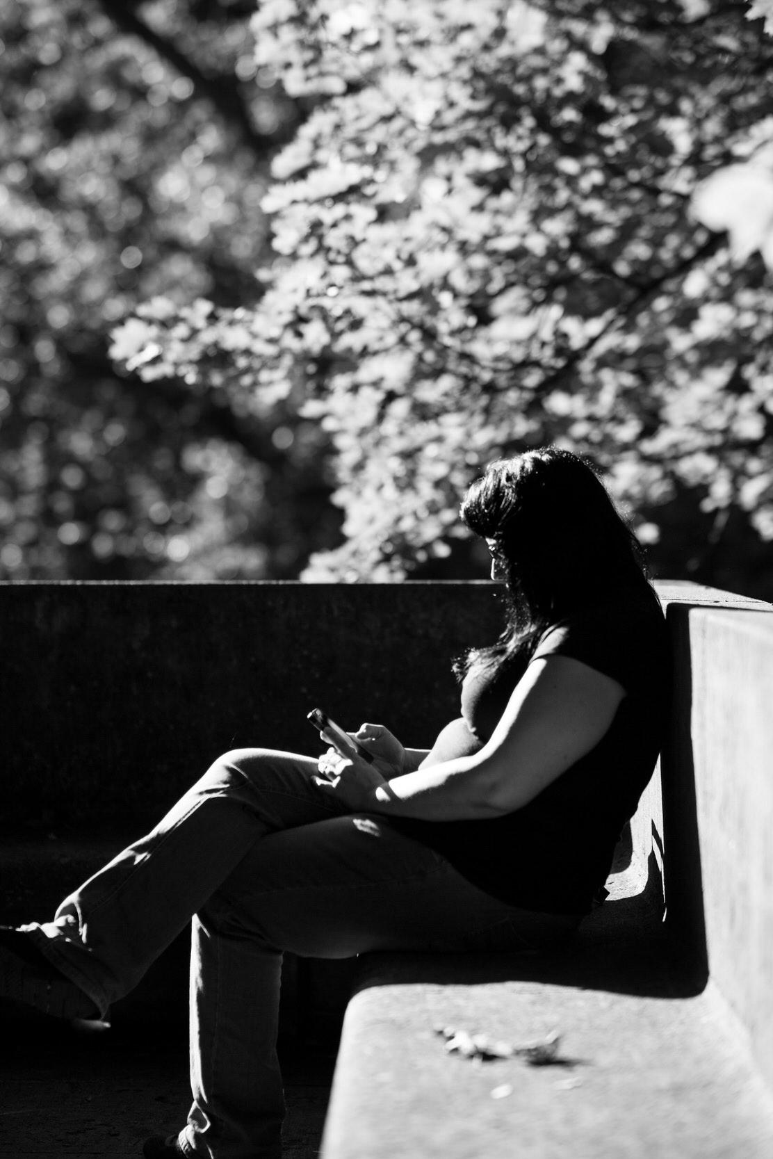 Portrait einer Frau unter Bäumen sitzend in schwarz - weiß.