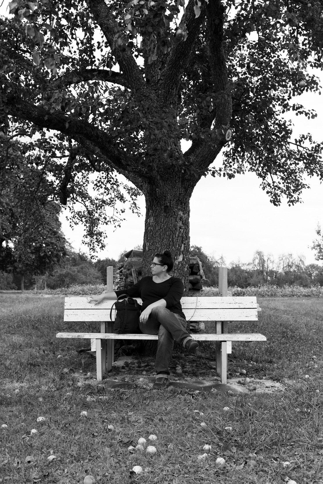 Portrait einer Frau unter einem Obstbaum auf einer Bank sitzend.