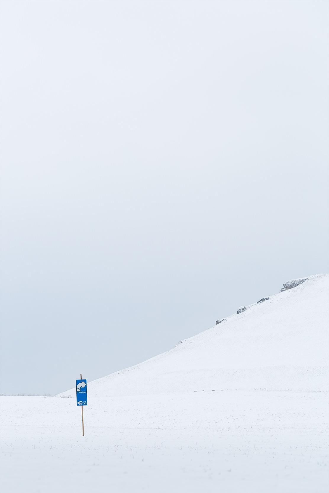 Blaues Schild mit Weghinweis für eine Langlaufloipe im Schnee.