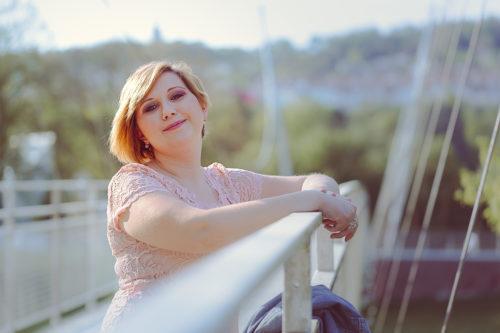 Frau lehnt an Brücke und lächelt den Betrachter an.