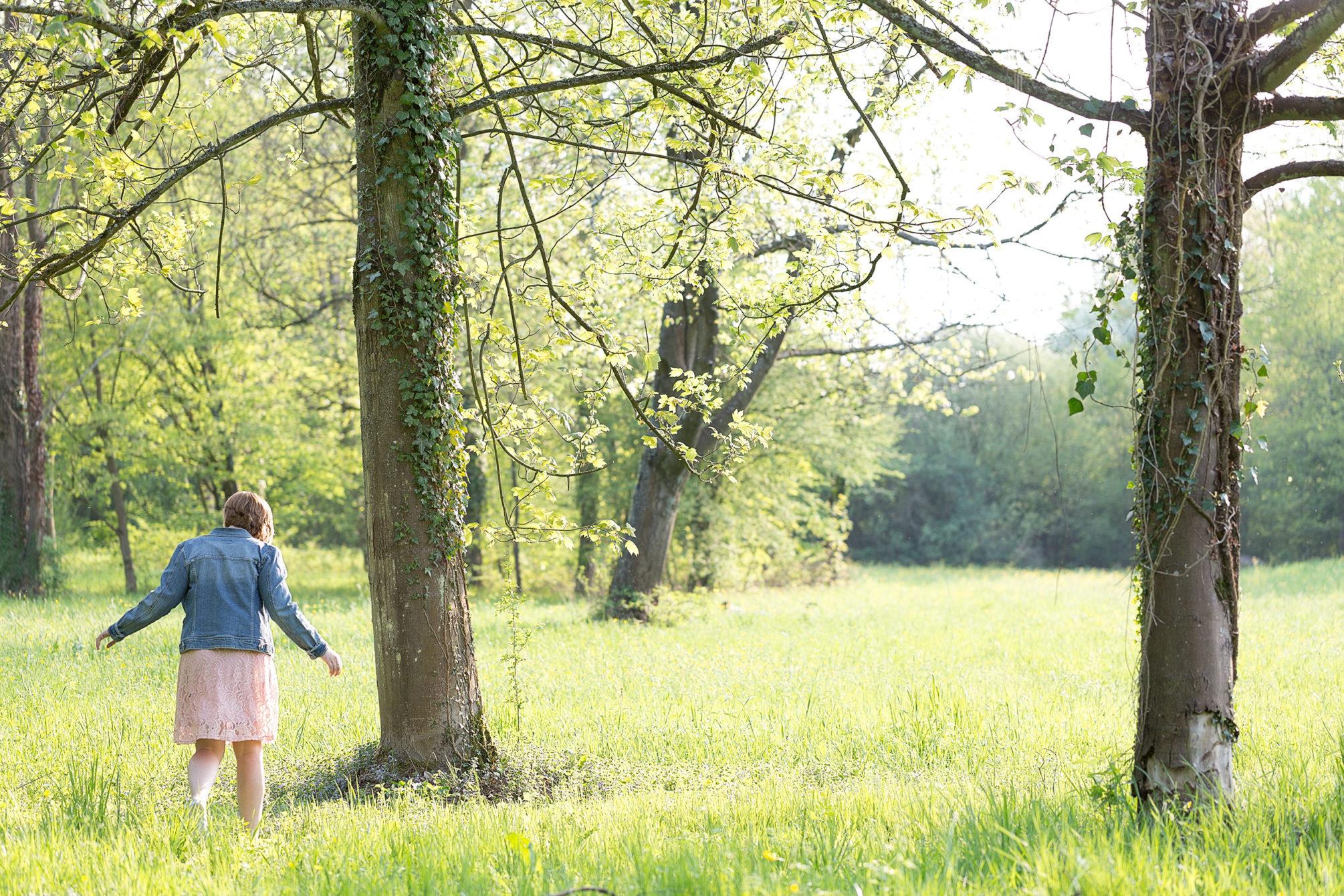 Frau läuft auf im hohen Gras eine Gruppe Bäume zu,
