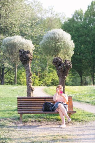 Frau sitzt auf Bank im Park und schminkt sich.