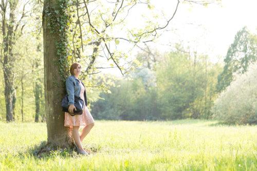 Frau lehnt an Baum mit Tasche im Arm.