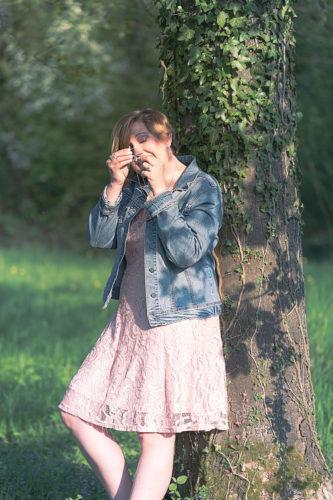Frau lehnt an Baum und schaut sich etwas in ihren Händen an.